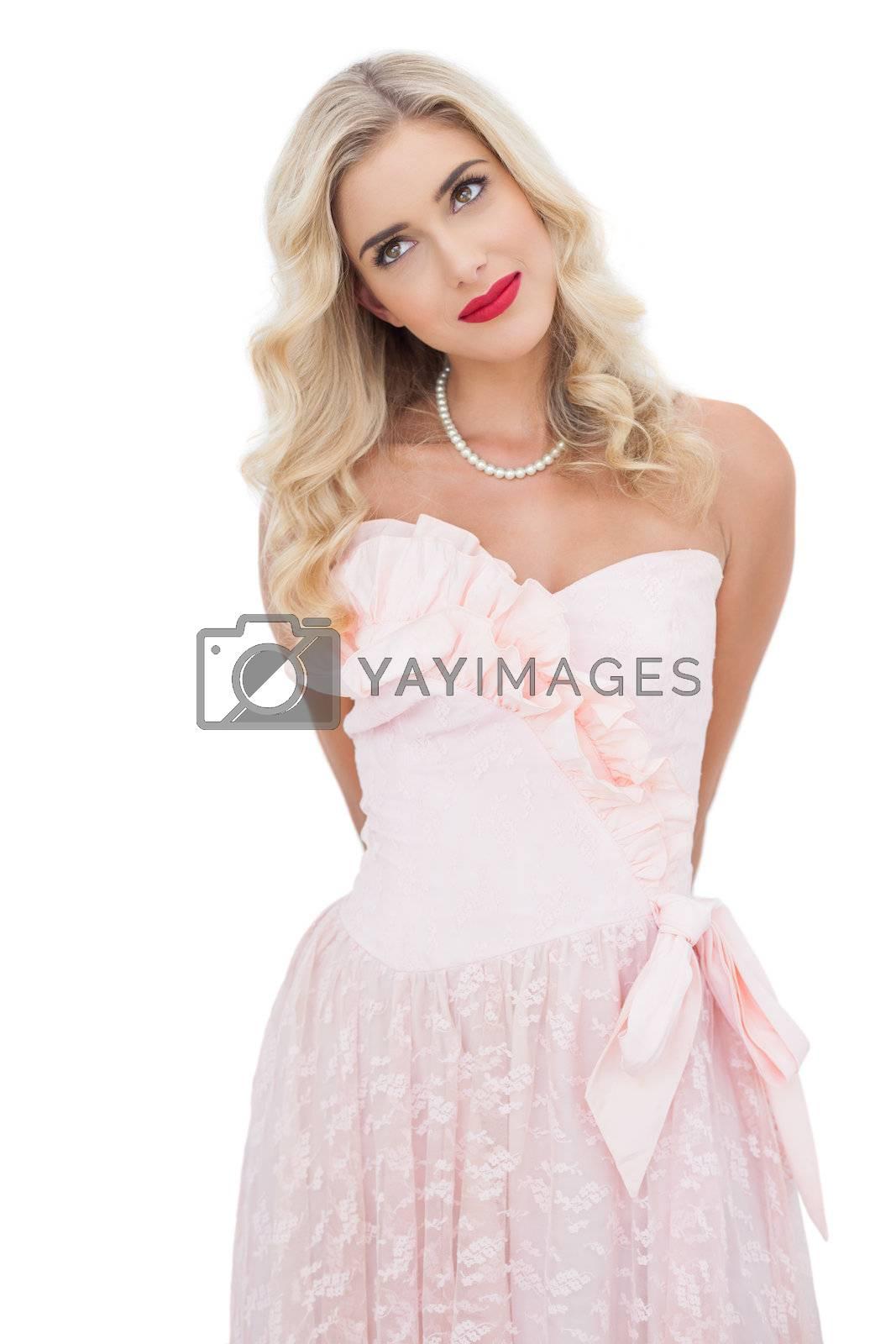 Content blonde model in pink dress posing looking away by Wavebreakmedia