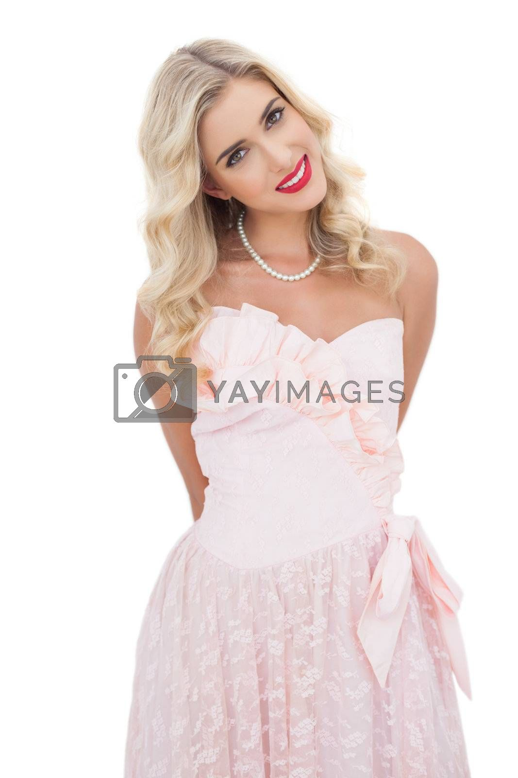 Happy blonde model in pink dress posing looking  by Wavebreakmedia