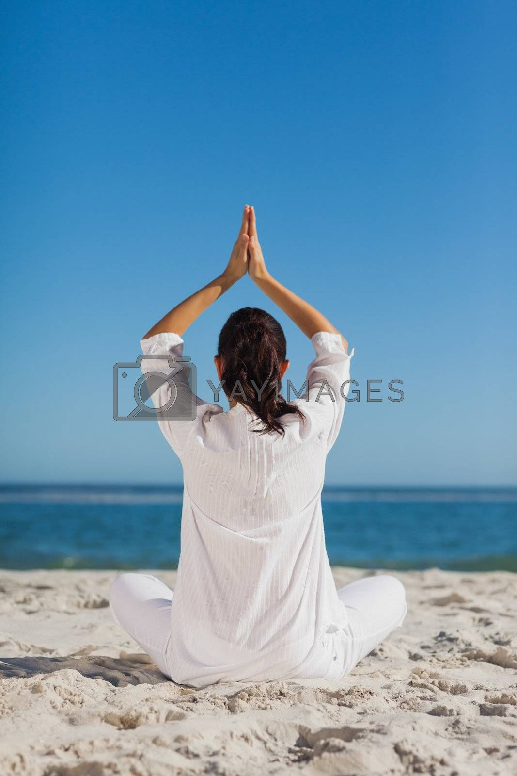 Brunette woman sitting back to camera practicing yoga by Wavebreakmedia