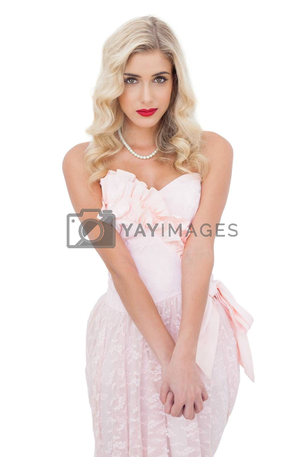 Unsmiling blonde model in pink dress posing looking at camera and holding her hands by Wavebreakmedia