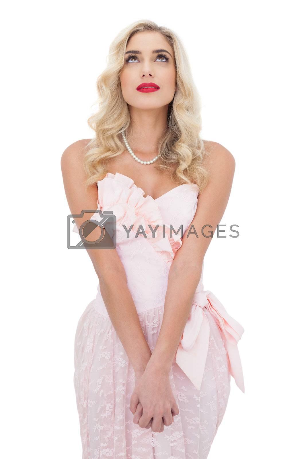 Wondering blonde model in pink dress posing holding hands and looking up by Wavebreakmedia