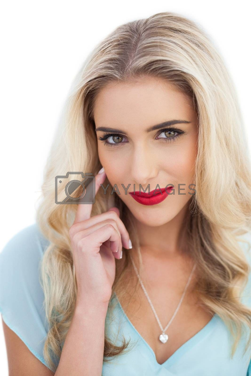 Portrait of an amused blonde woman in blue dress looking at camera by Wavebreakmedia