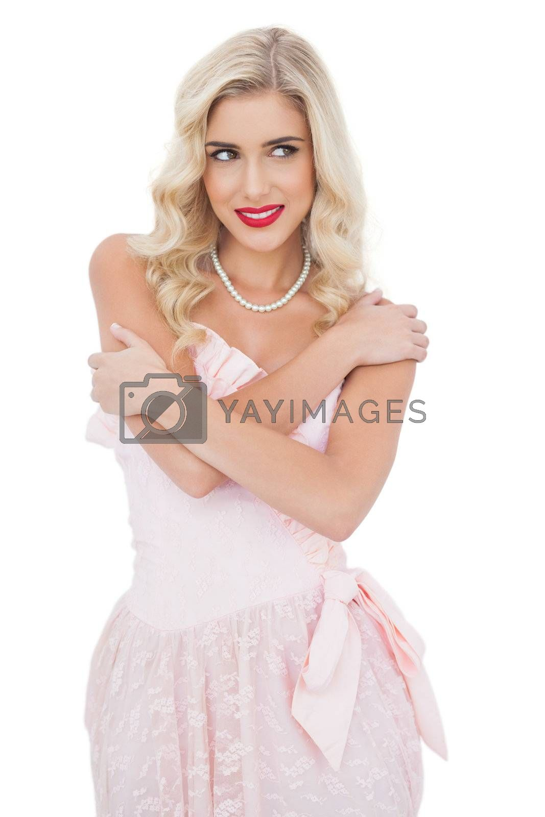 Delighted blonde model in pink dress posing holding her shoulders and looking away by Wavebreakmedia