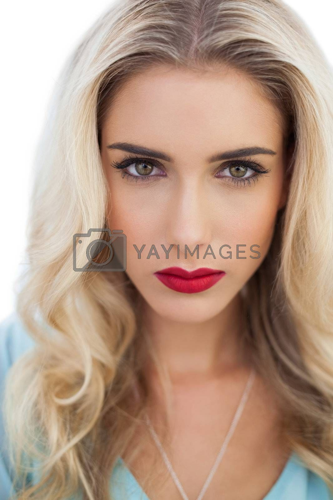Portrait of a severe blonde woman in blue dress looking at camera by Wavebreakmedia