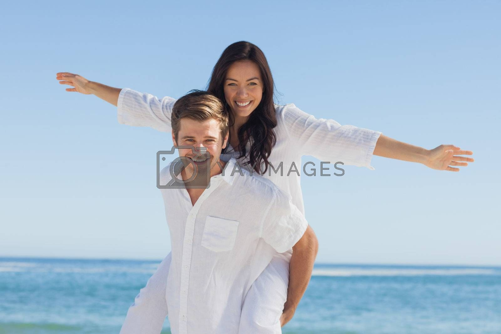 Woman sitting on mans back smiling at camera by Wavebreakmedia
