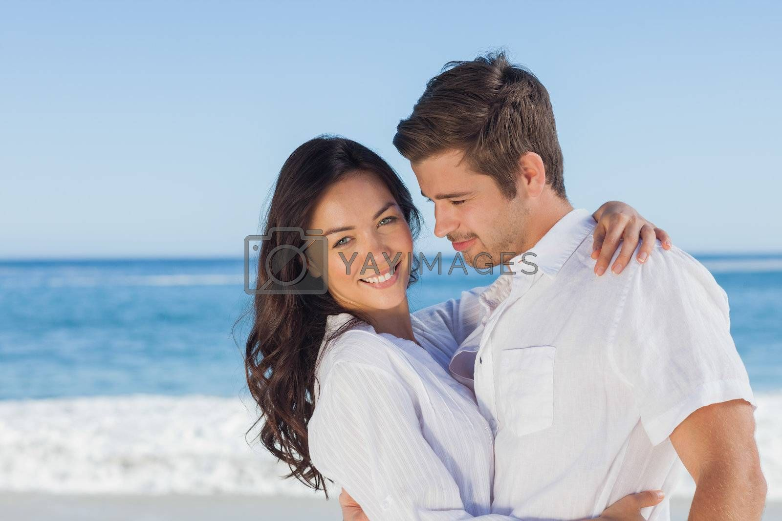 Young couple embracing and posing on the beach  by Wavebreakmedia