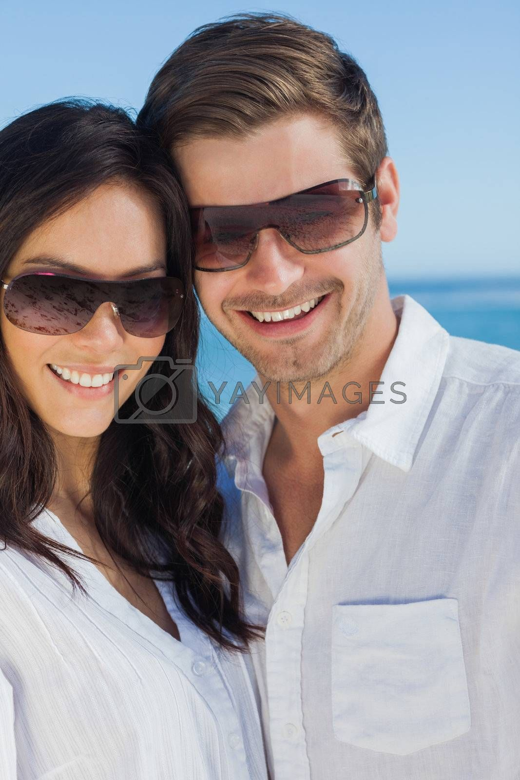 Happy couple wearing sunglasses and smiling at camera by Wavebreakmedia