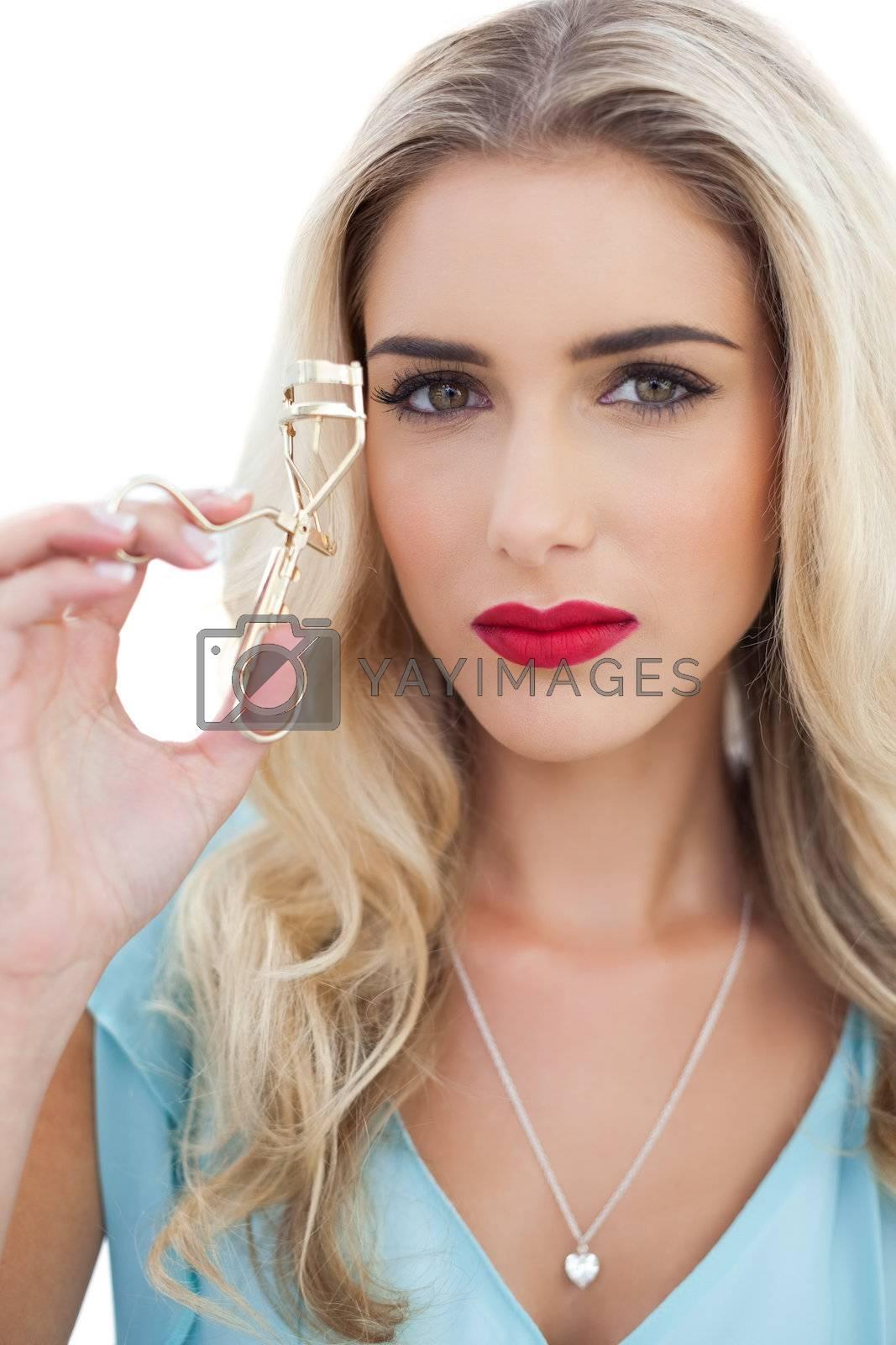Serious blonde model in blue dress holding a eyelash curler by Wavebreakmedia