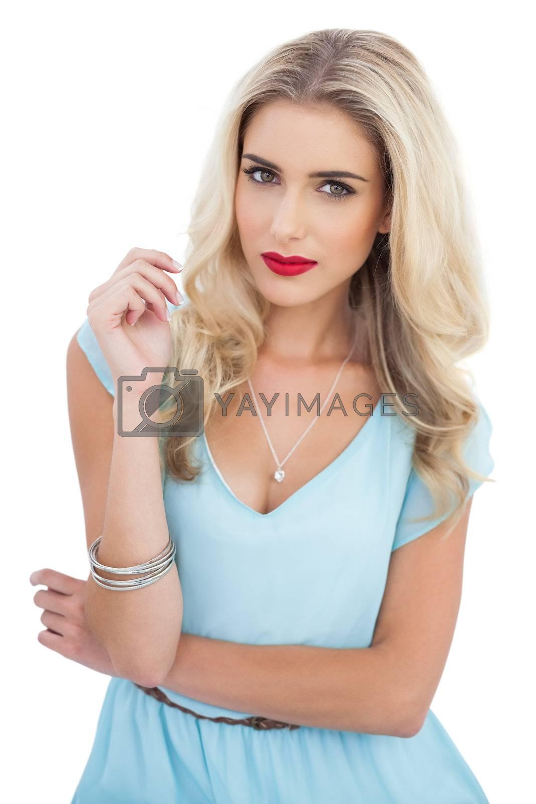Dreamy blonde model in blue dress looking at camera by Wavebreakmedia