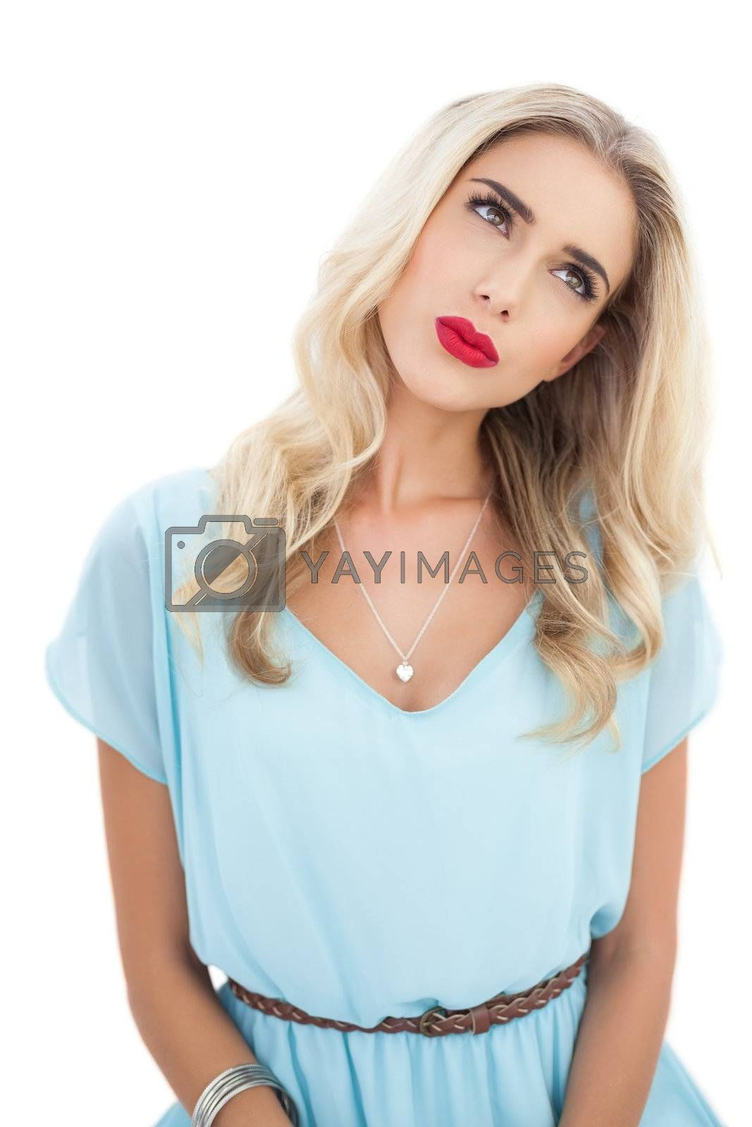 Concentrated blonde model in blue dress looking away by Wavebreakmedia
