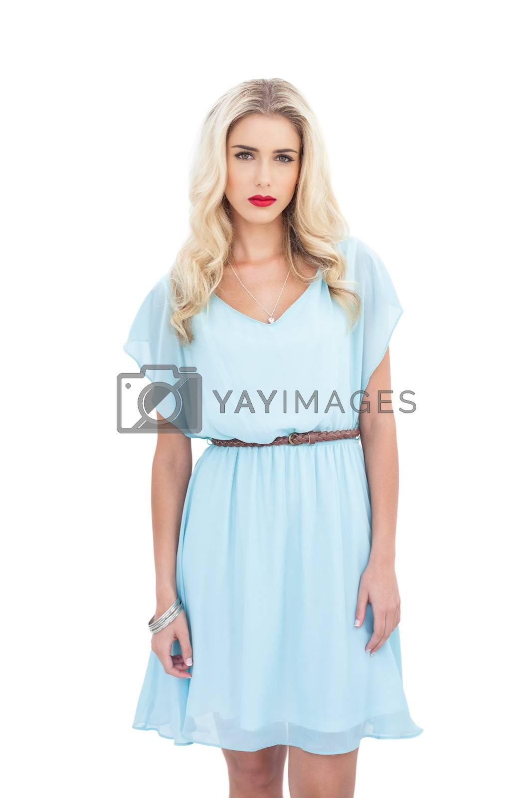 Charming blonde model in blue dress looking at camera by Wavebreakmedia