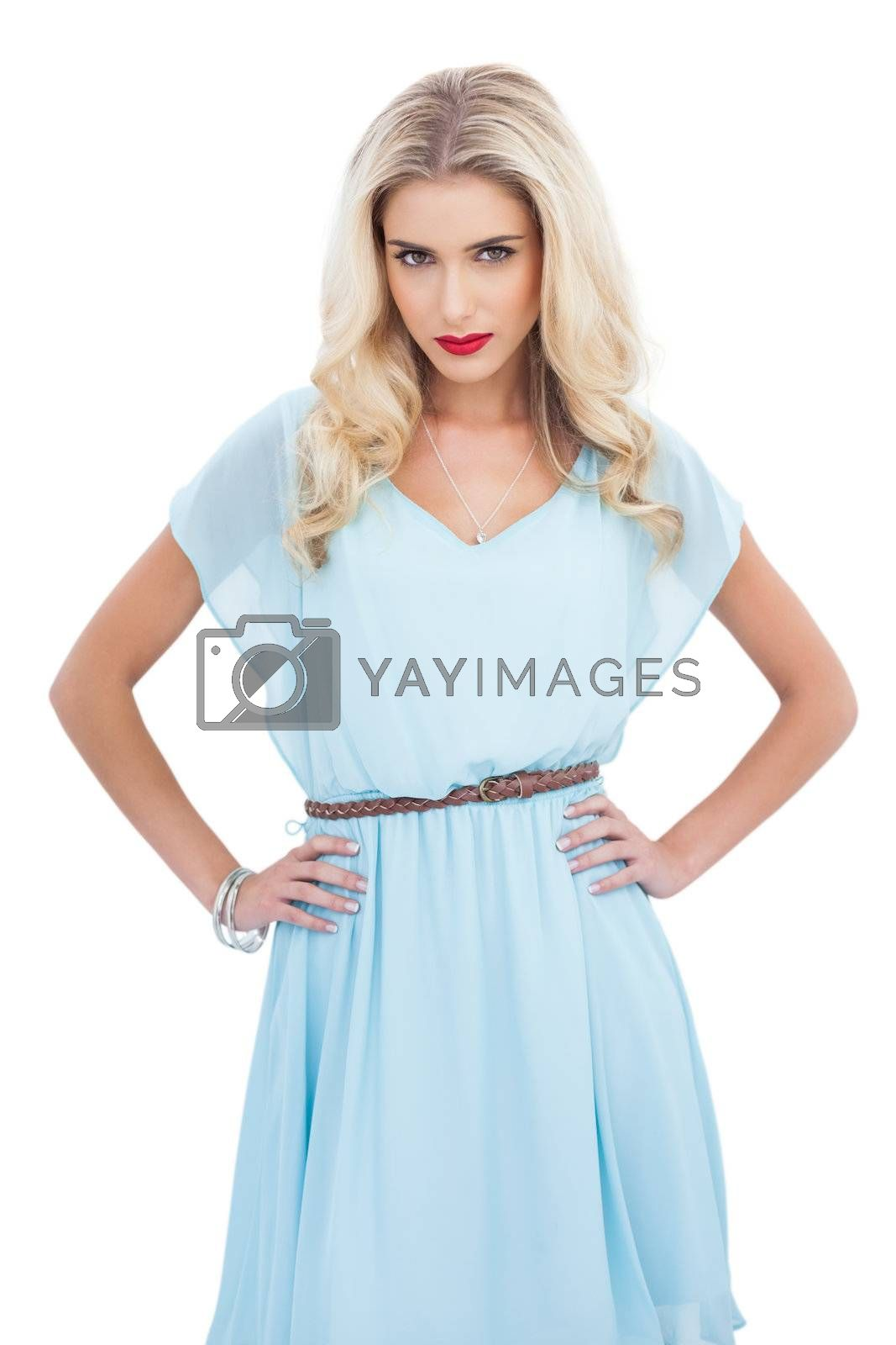 Lovely blonde model in blue dress posing with hands on the hips by Wavebreakmedia