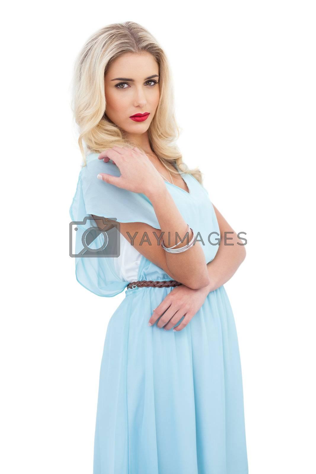 Serious blonde model in blue dress posing holding her shoulder by Wavebreakmedia