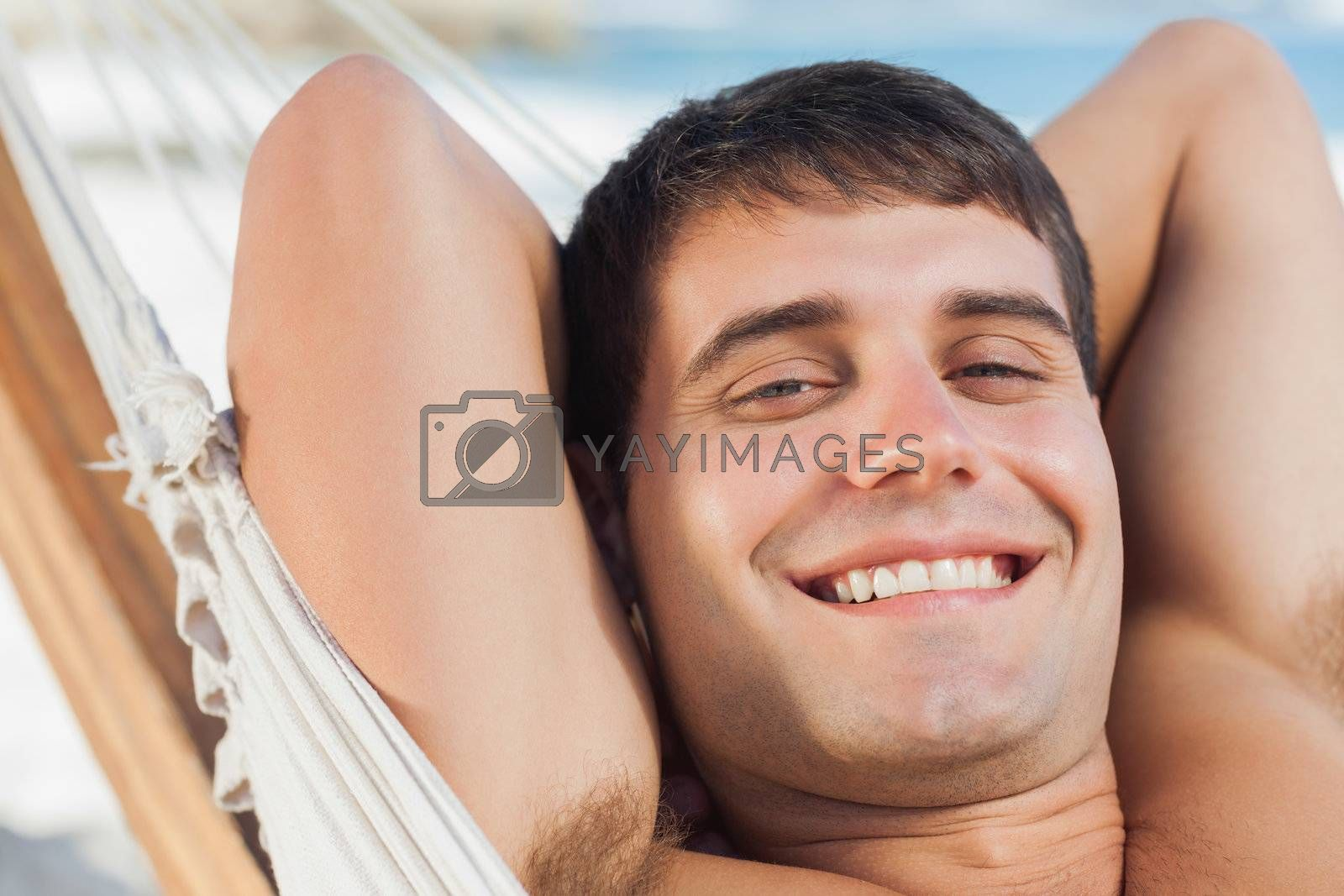 Smiling man relaxing in hammock by Wavebreakmedia