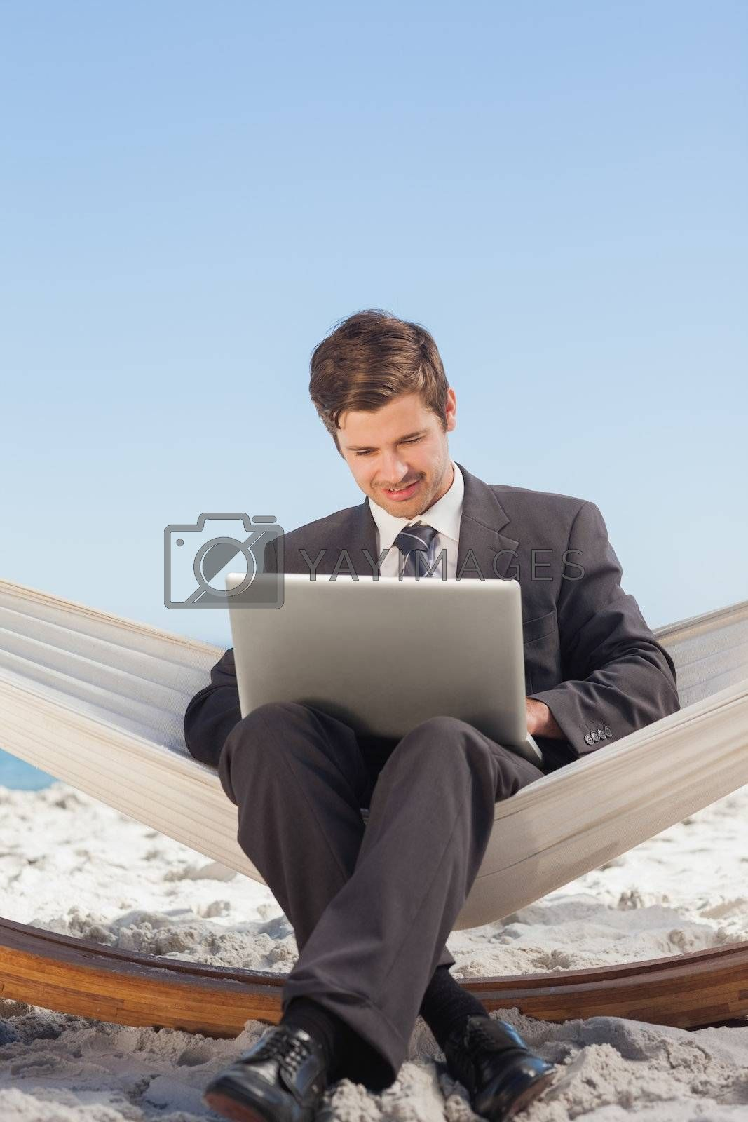 Businessman typing on his laptop in a hammock and smiling by Wavebreakmedia