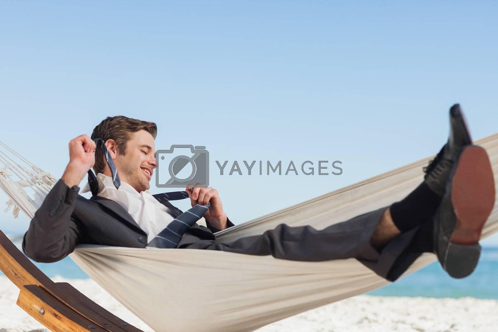 Smiling businessman lying in hamock taking off his tie by Wavebreakmedia