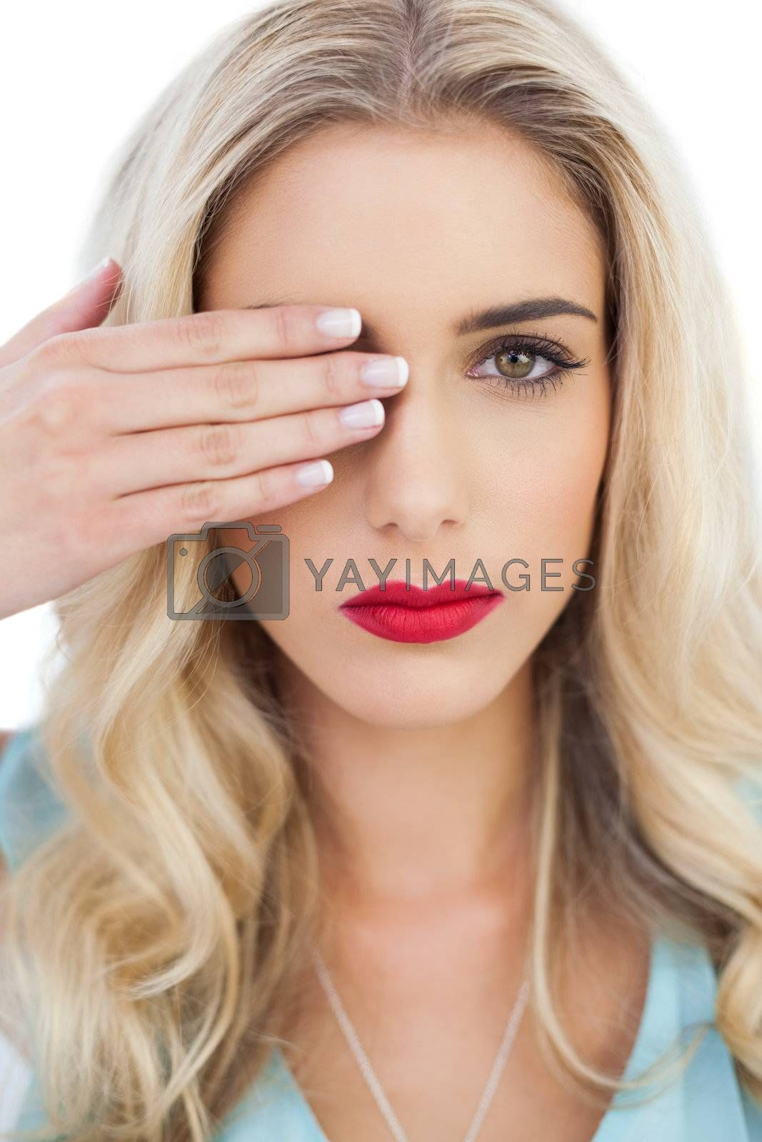 Blonde model in blue dress looking at camera with one eye and hidding the other with her hand by Wavebreakmedia
