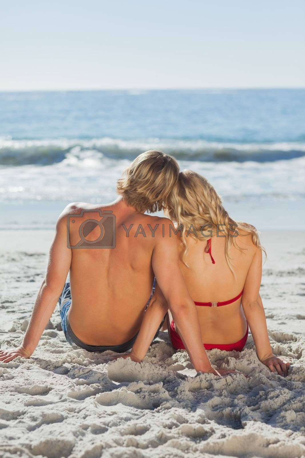 Rear view of a happy tanned couple sitting by Wavebreakmedia