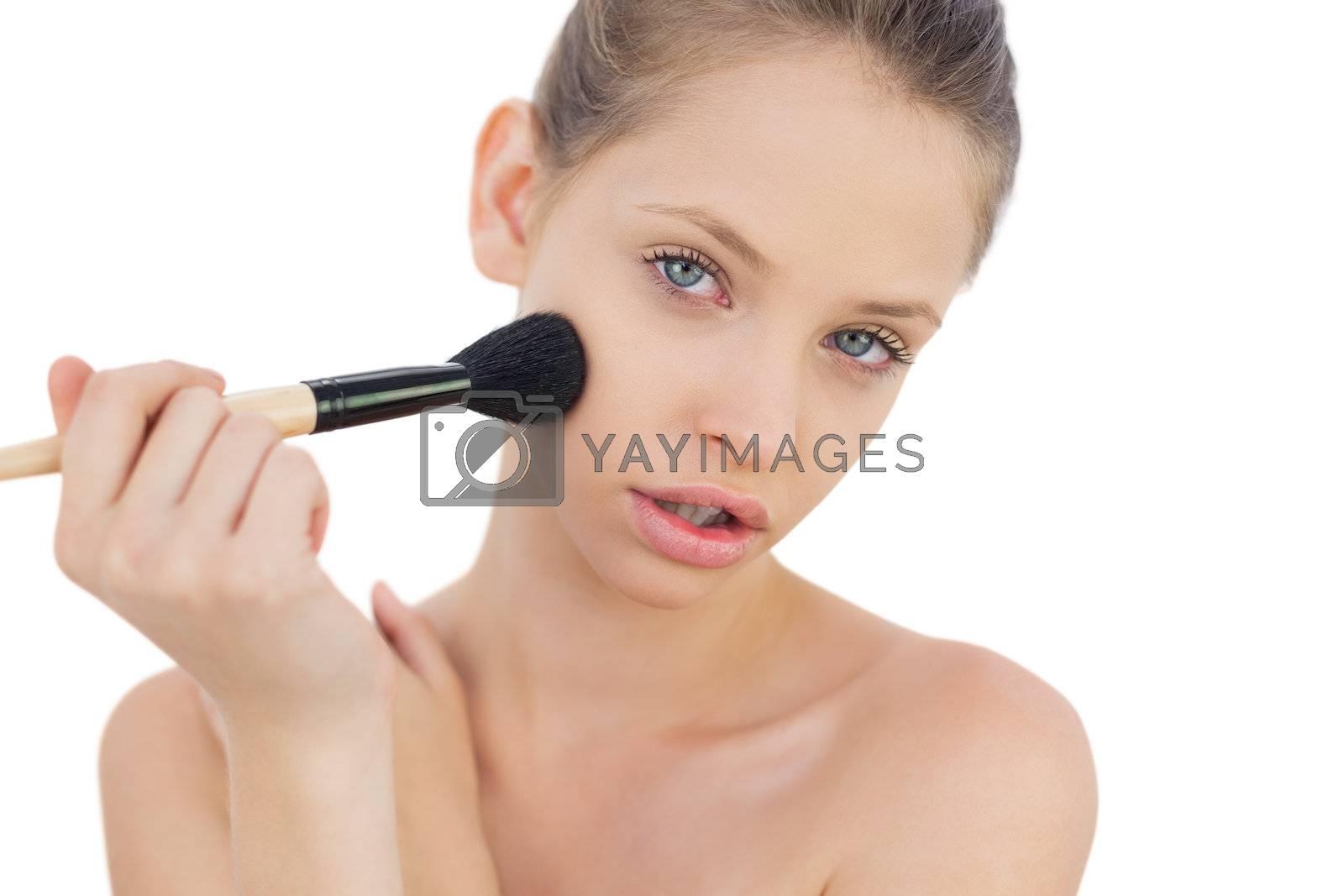 Serious brunette model applying powder on her cheek by Wavebreakmedia
