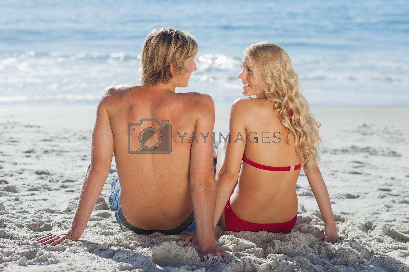 Happy couple sitting on beach by Wavebreakmedia