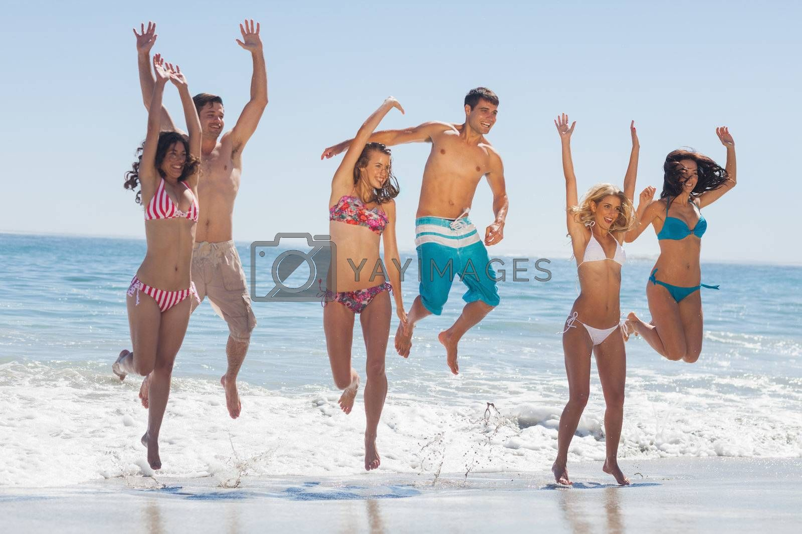 Happy friends jumping on the beach  by Wavebreakmedia