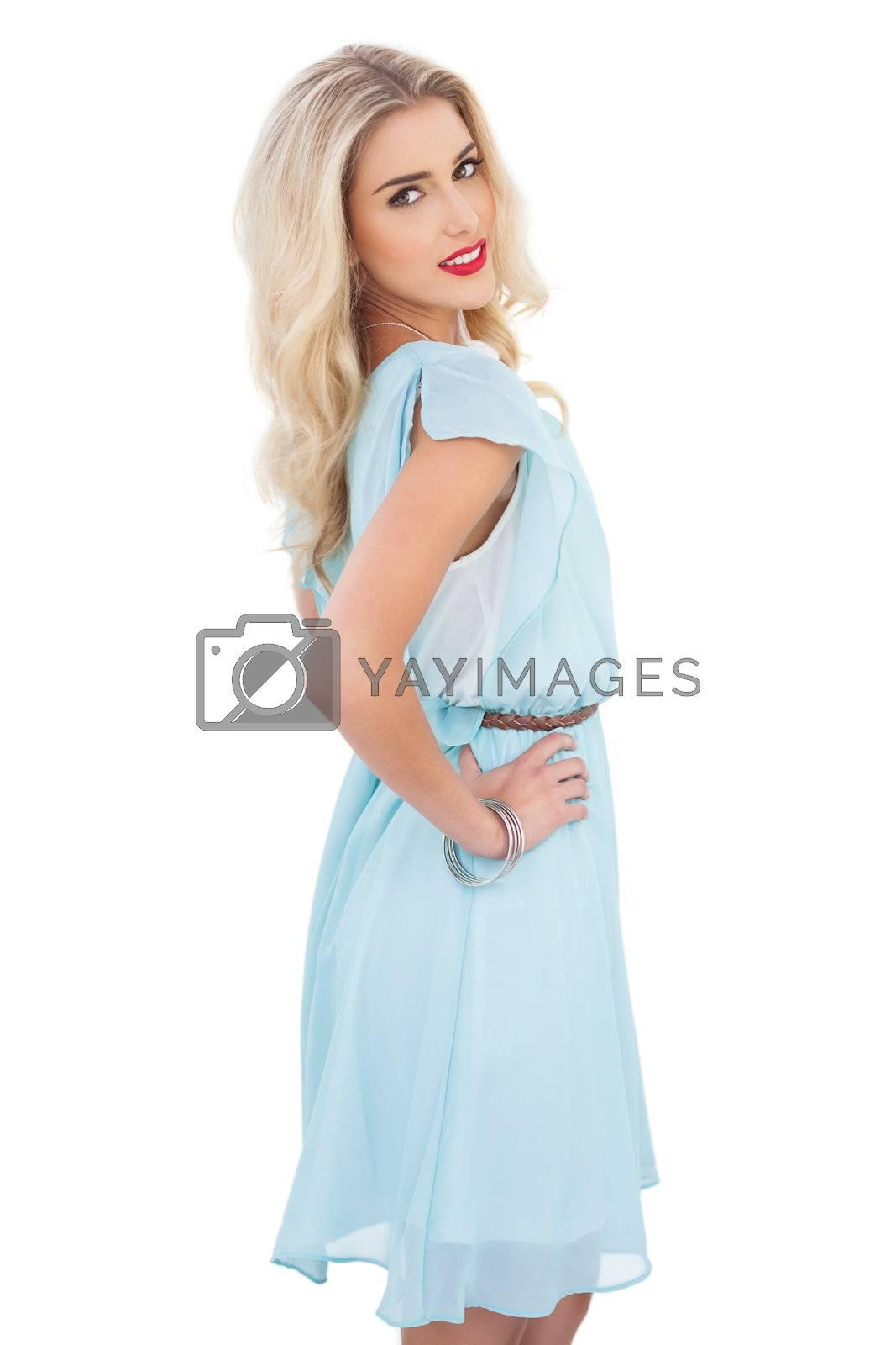 Pretty blonde model in blue dress posing hand on the hip by Wavebreakmedia