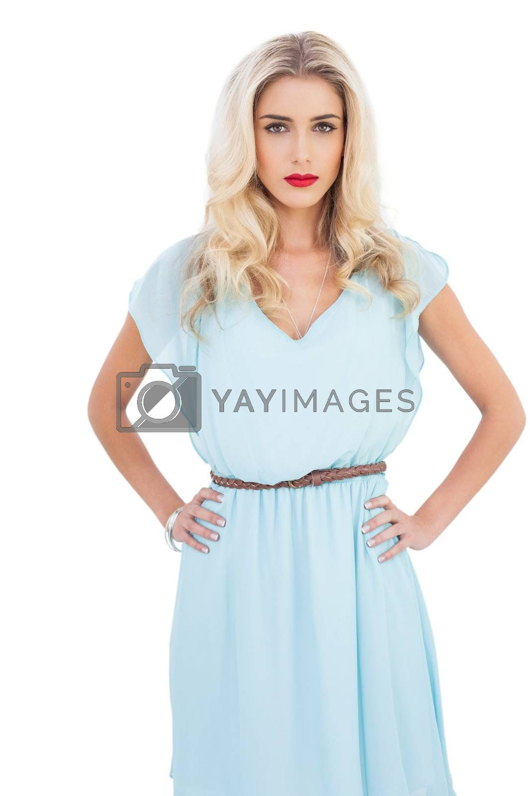 Contemplative blonde model in blue dress posing hands on the hips by Wavebreakmedia
