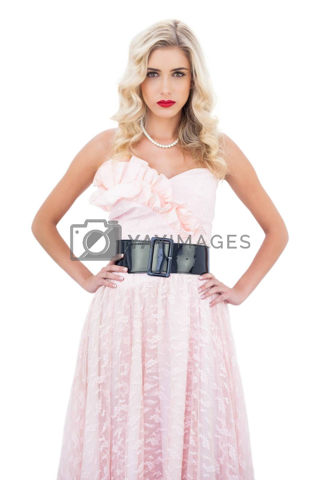 Stern blonde model in pink dress posing hands on the hips and looking at camera by Wavebreakmedia