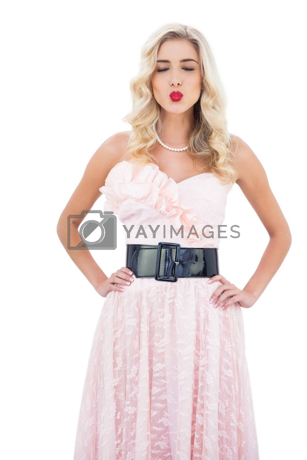 Wondering blonde model in pink dress closing her eyes and posing hands on the hips by Wavebreakmedia