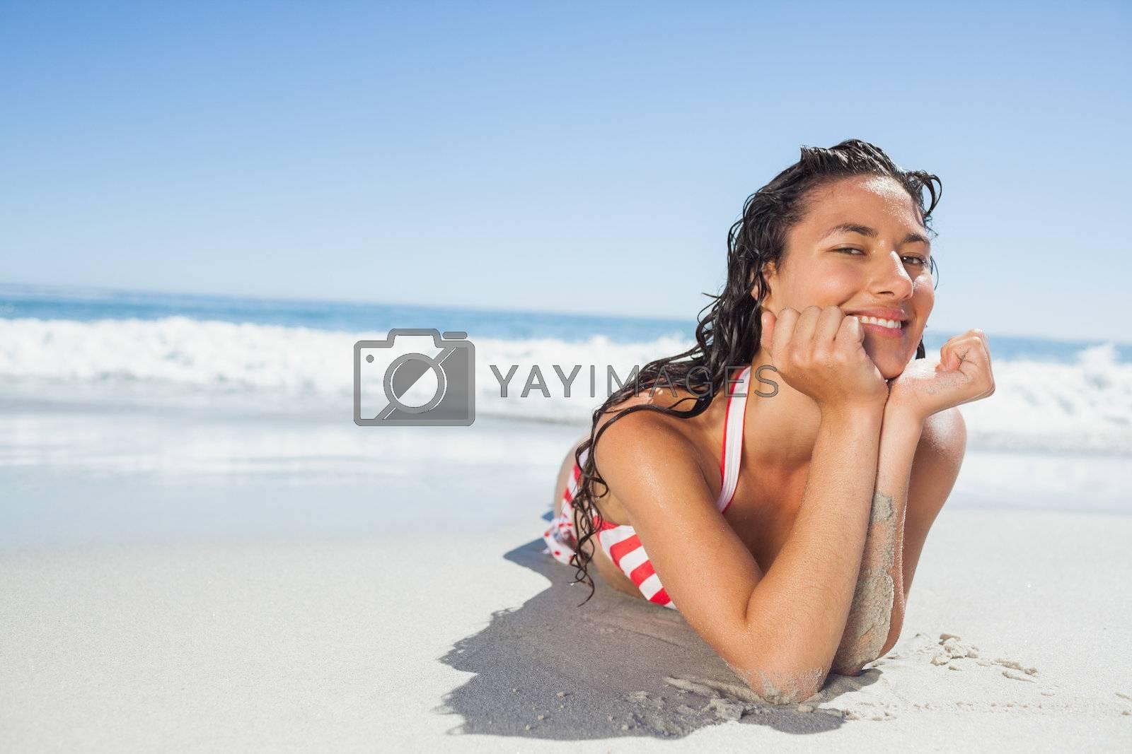 Smiling woman lying down on beach by Wavebreakmedia