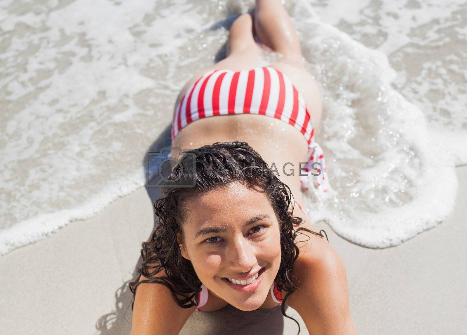 High angle view of smiling woman lying down on beach by Wavebreakmedia