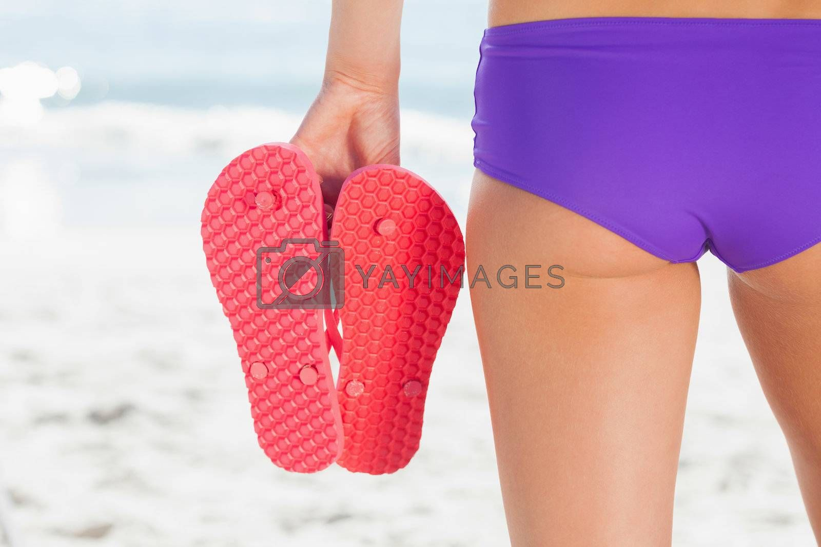 Rear view of a young woman holding flip flops by Wavebreakmedia