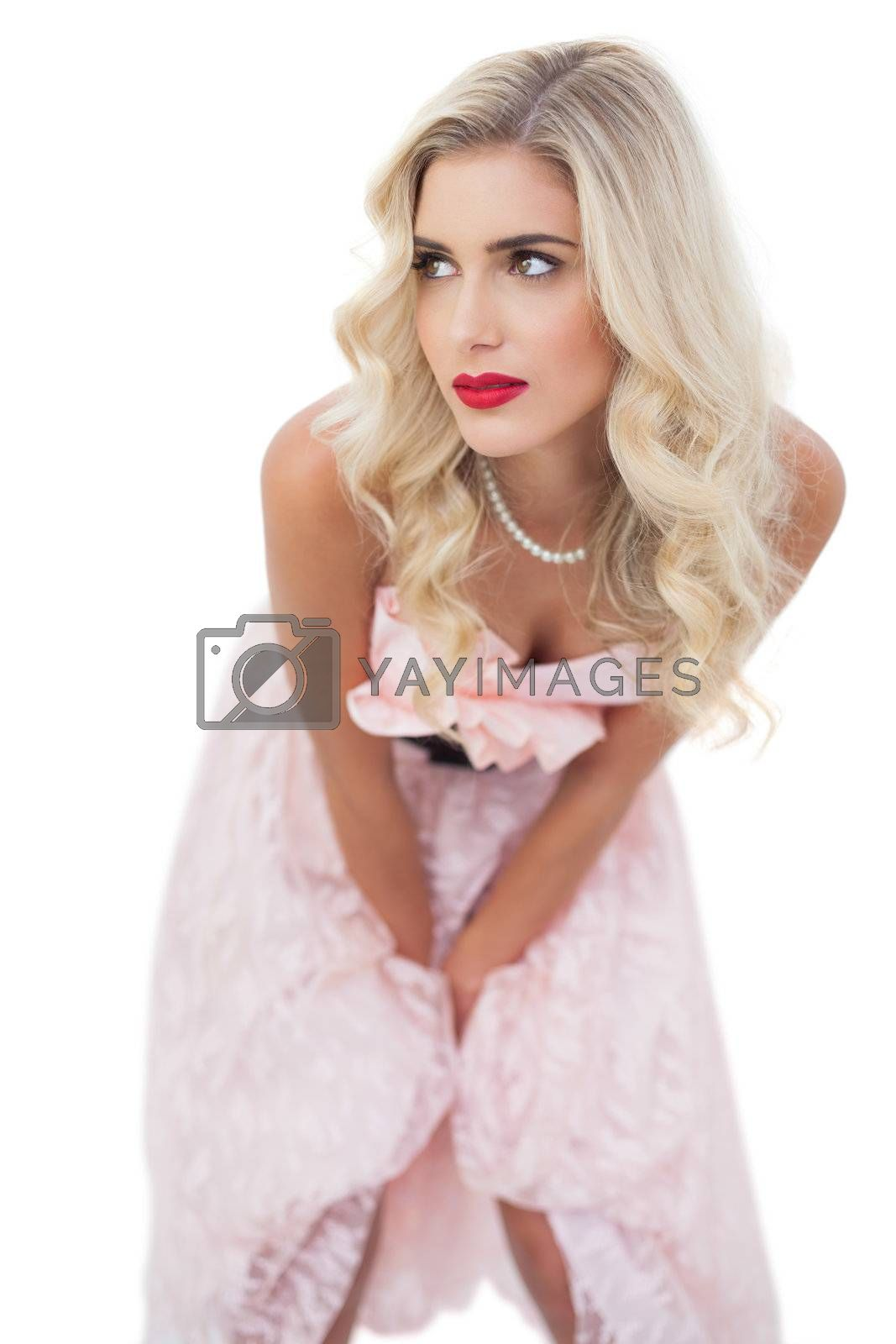 Thinking blonde model in pink dress posing hands on the thighs by Wavebreakmedia
