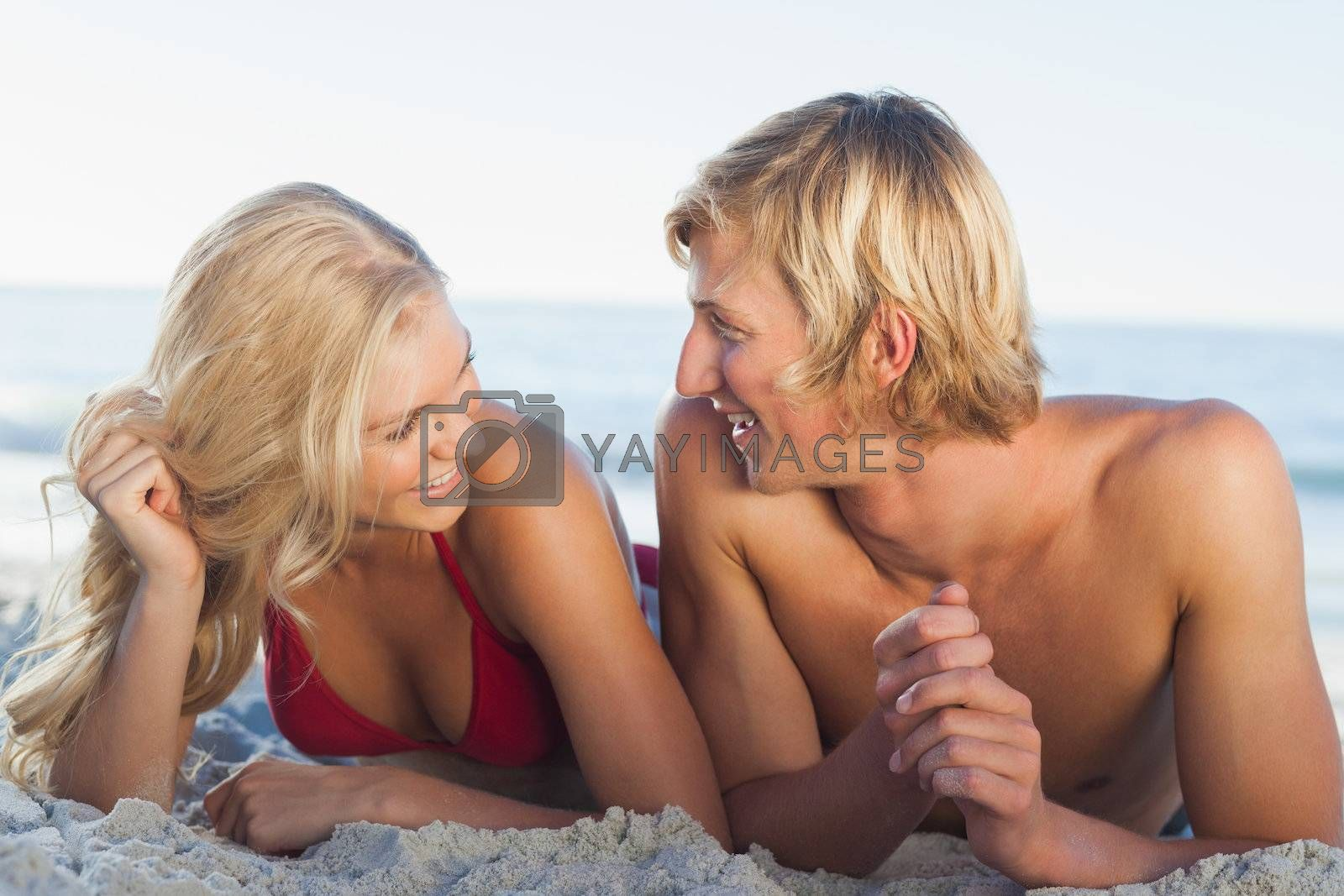 Smiling couple facing each other and lying by Wavebreakmedia