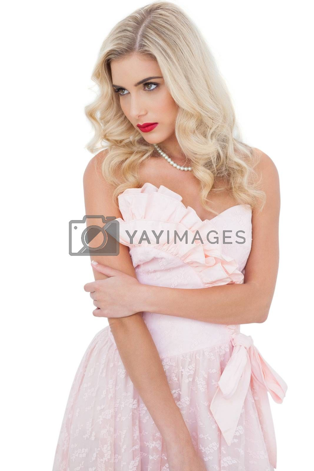 Concentrated blonde model in pink dress posing holding her arm by Wavebreakmedia