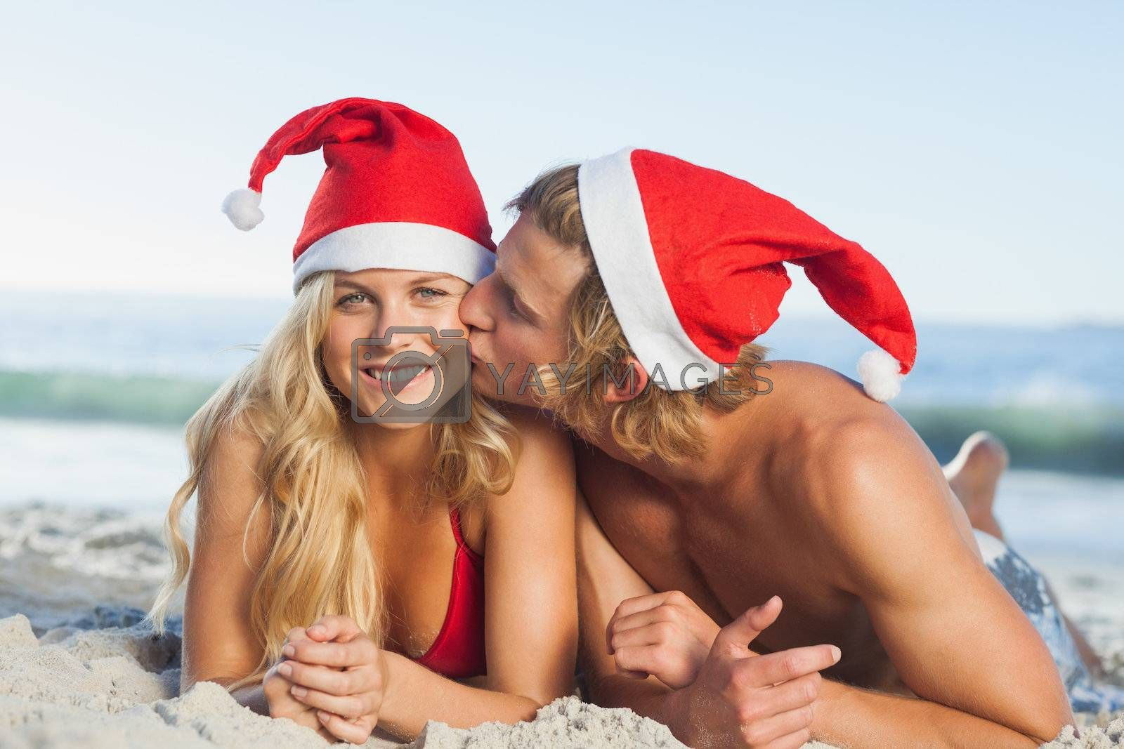 Man giving kiss to partner wearing christmas hats by Wavebreakmedia