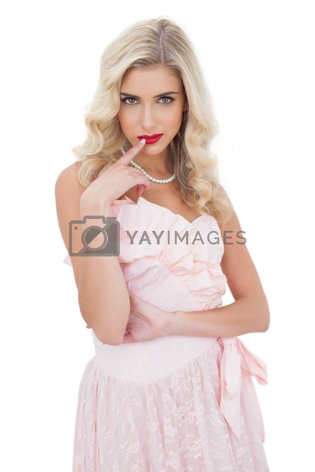 Amused blonde model in pink dress posing a finger on the mouth by Wavebreakmedia