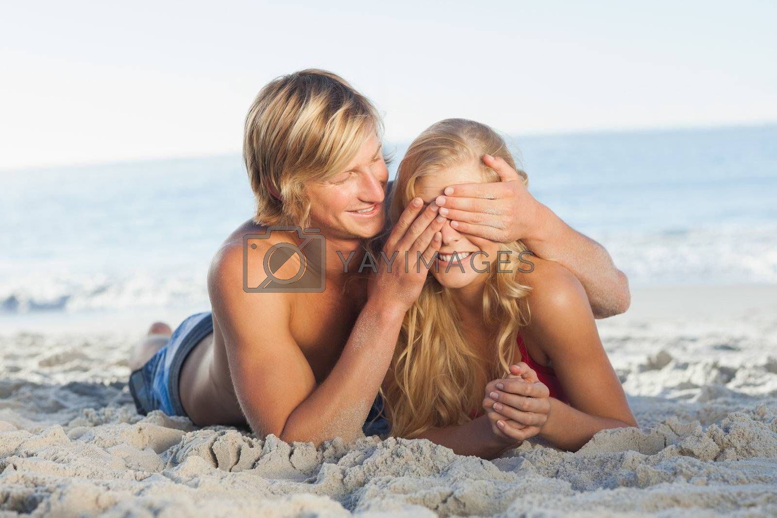 Man covering girlfriends eyes lying on the beach by Wavebreakmedia