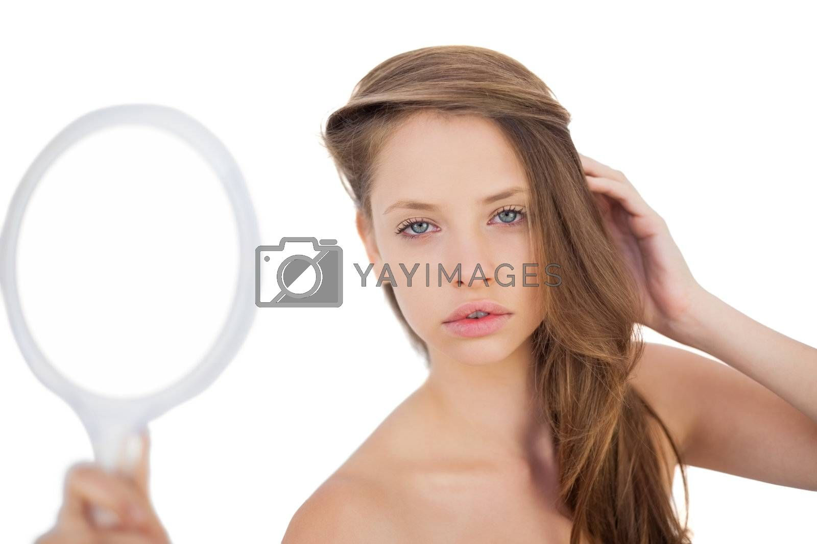 Calm brunette model posing holding a mirror by Wavebreakmedia