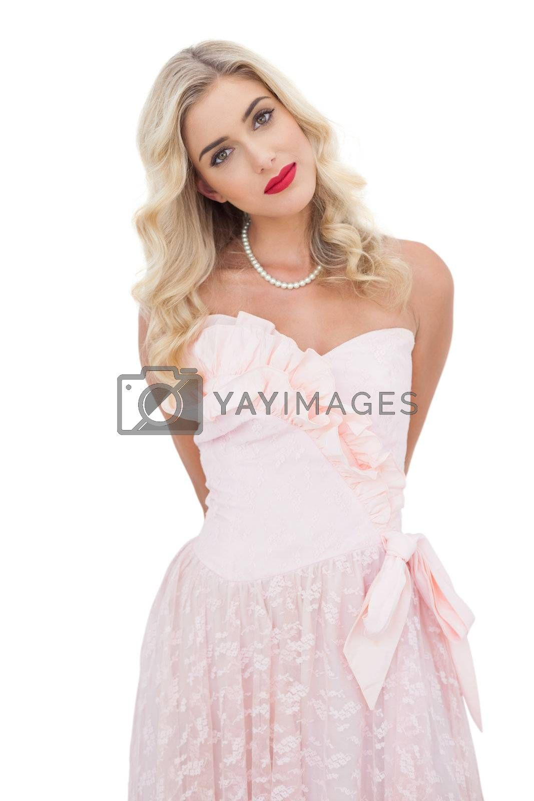 Content blonde model in pink dress posing looking at camera by Wavebreakmedia