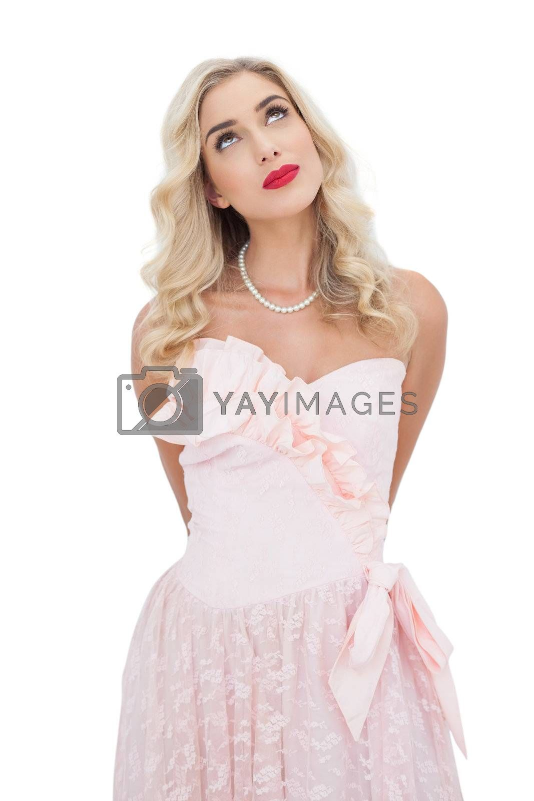 Thinking blonde model in pink dress posing looking away by Wavebreakmedia
