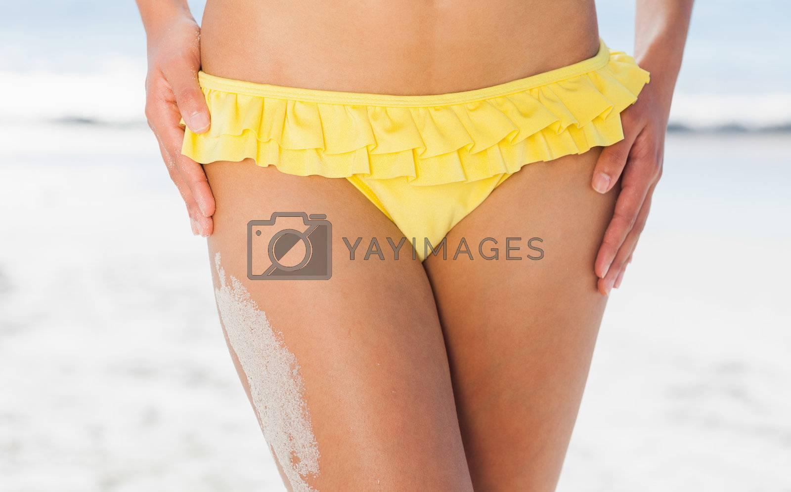 Mid section of fit woman in yellow bikini by Wavebreakmedia