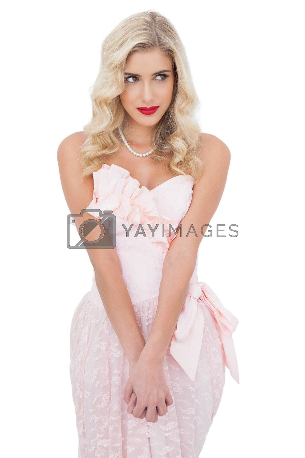 Concentrated blonde model in pink dress posing holding her hands and looking away by Wavebreakmedia