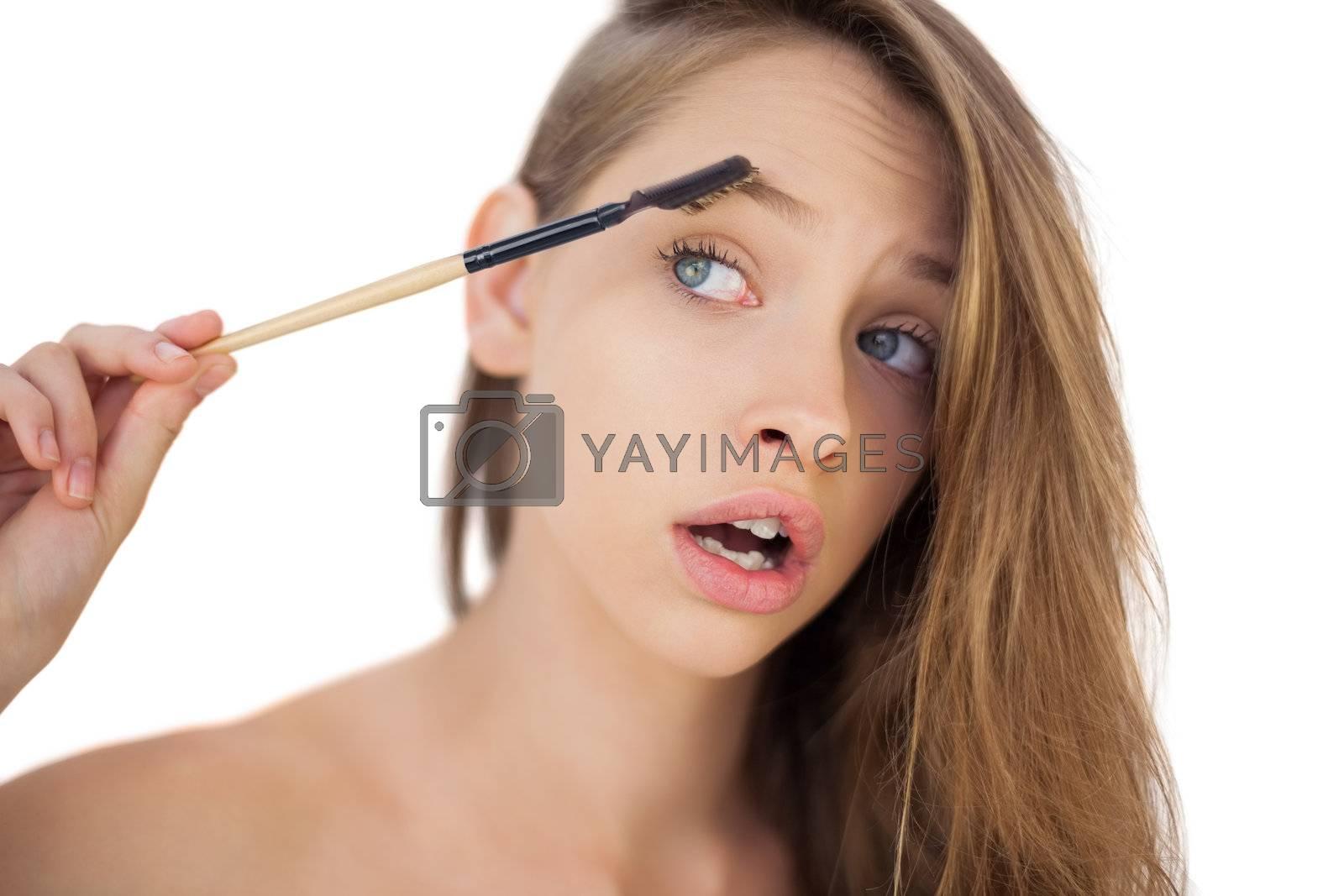 Puzzled brunette model brushing her eyebrows by Wavebreakmedia
