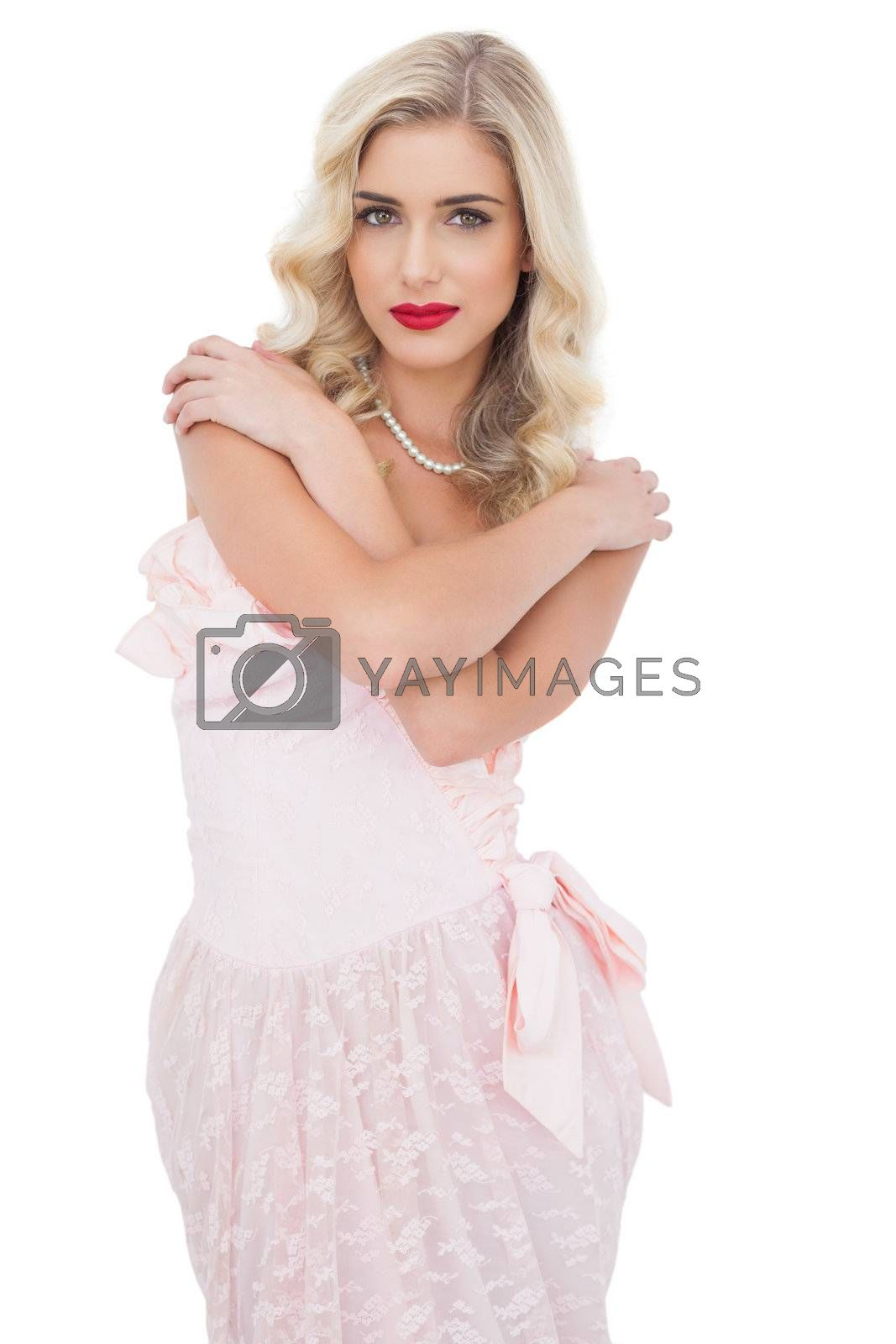 Serious blonde model in pink dress posing holding her shoulders and looking at camera by Wavebreakmedia