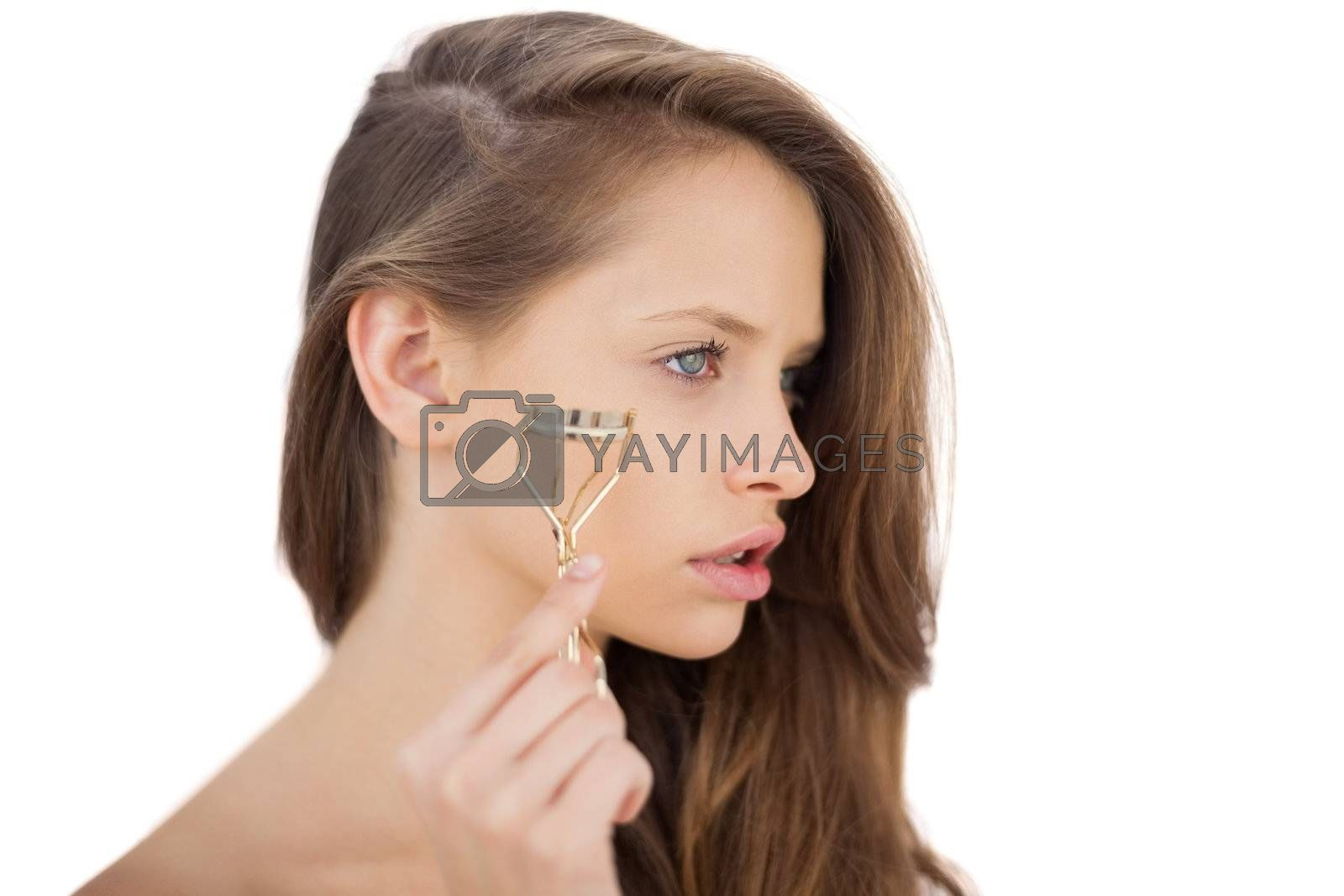 Unsmiling brunette model holding an eyelash curler by Wavebreakmedia