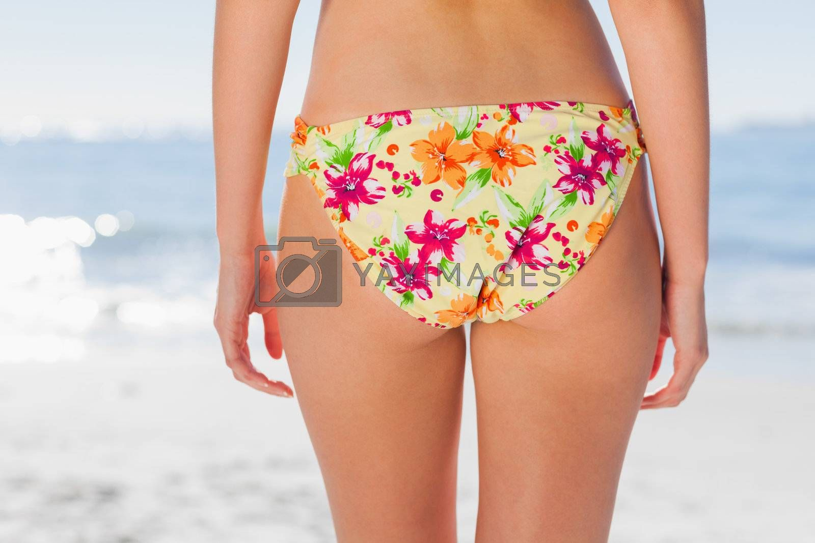 Woman in floral bikini on beach by Wavebreakmedia
