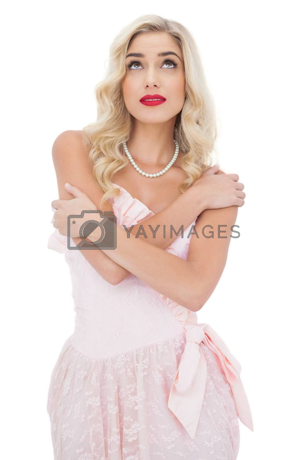 Pensive blonde model in pink dress posing holding her shoulders and looking up by Wavebreakmedia
