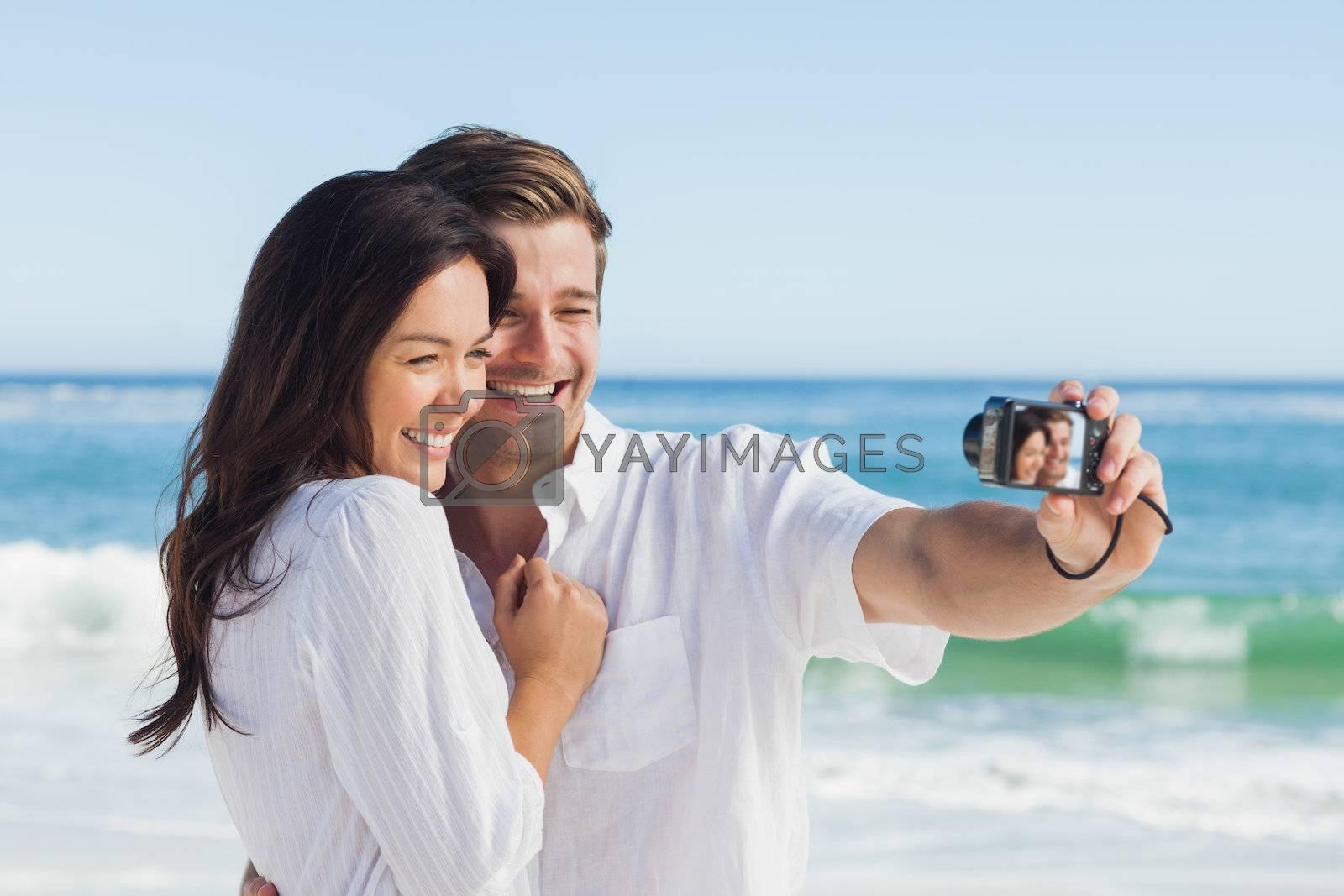 Happy couple taking a photo by Wavebreakmedia