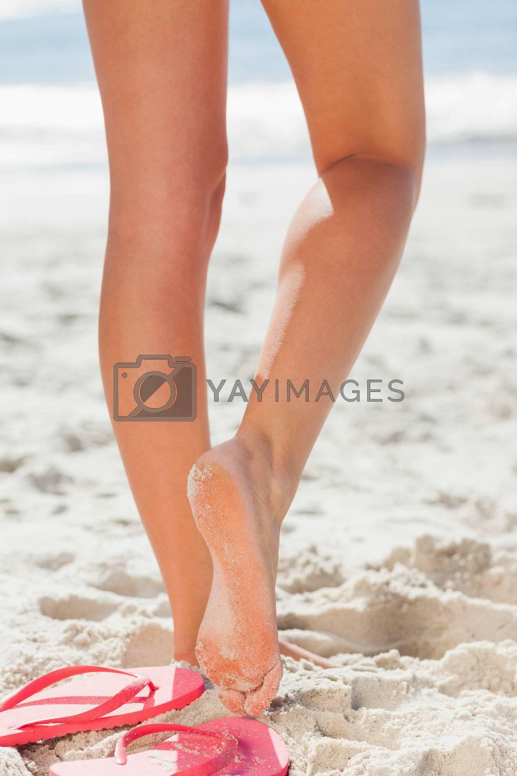 Womans legs on beach by Wavebreakmedia